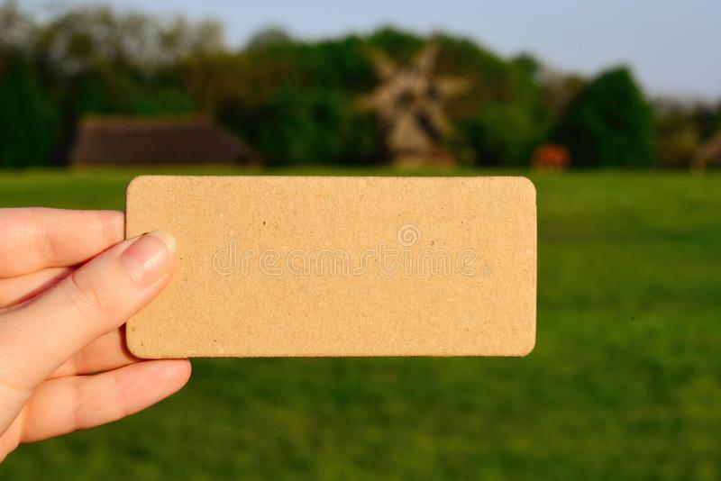 Girl holding card in a field with windmills and a road in sunny stock image