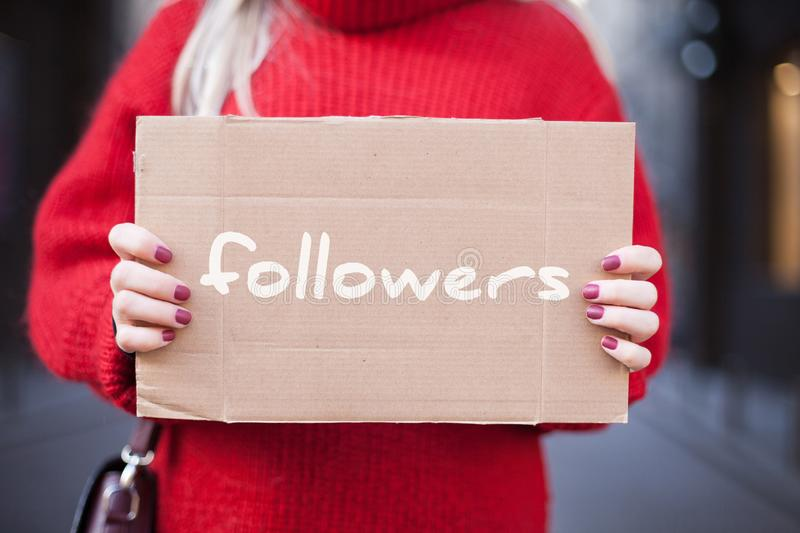 The girl is holding a cardboard tablet in her hands with the inscription `followers. stock photography
