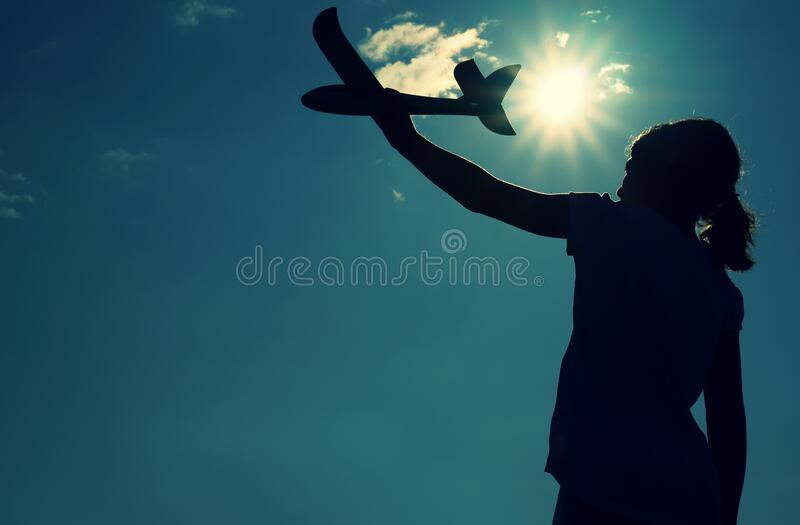 Girl holding a children`s plane in outstretched hand against the background of the sun - concept of success, desire for a dream, royalty free stock photography