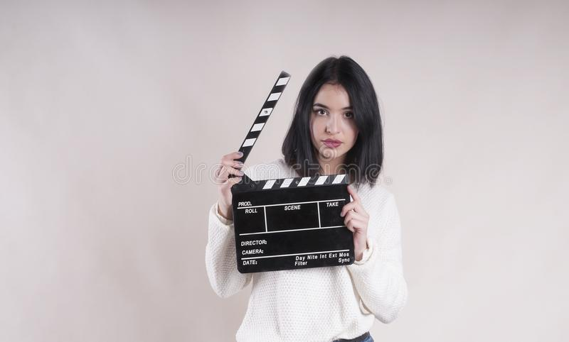 Girl is holding a clapperboard and posing. Girl is holding a clapperboard and posing royalty free stock images