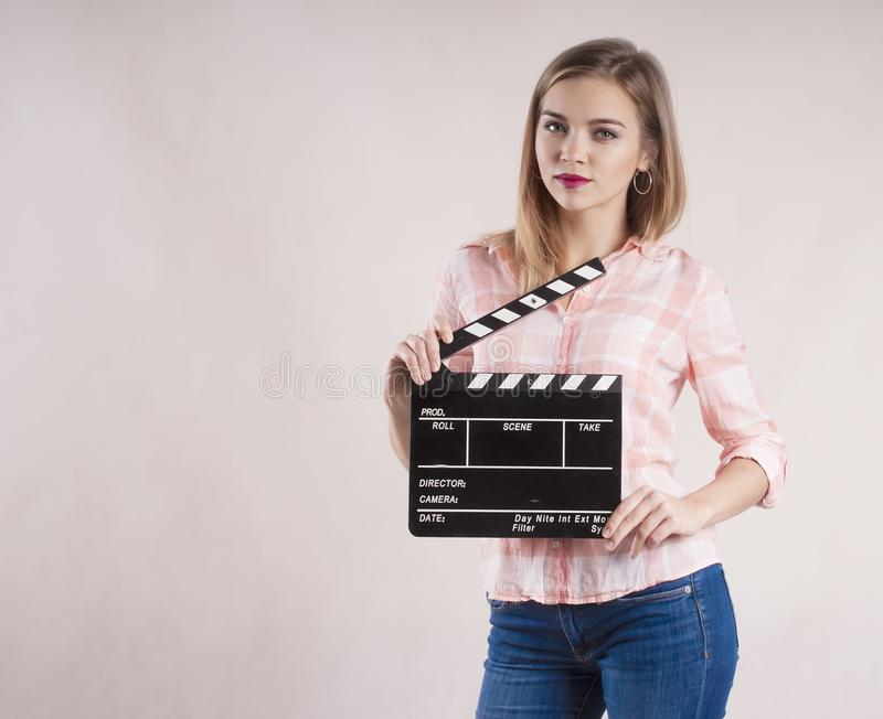 Girl is holding a clapperboard and posing. on white background. Girl is holding a clapperboard and posing background stock images