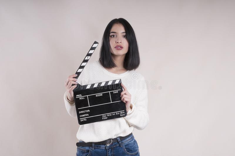 Girl is holding a clapperboard and posing. Girl is holding a clapperboard and posing commercial royalty free stock photo