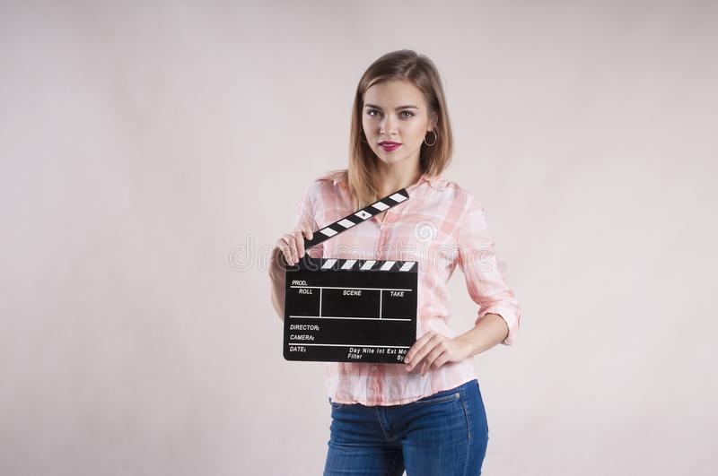 Girl is holding a clapperboard and posing Isolated on white background. Girl is holding clapperboard posing. Isolated on white background royalty free stock photos