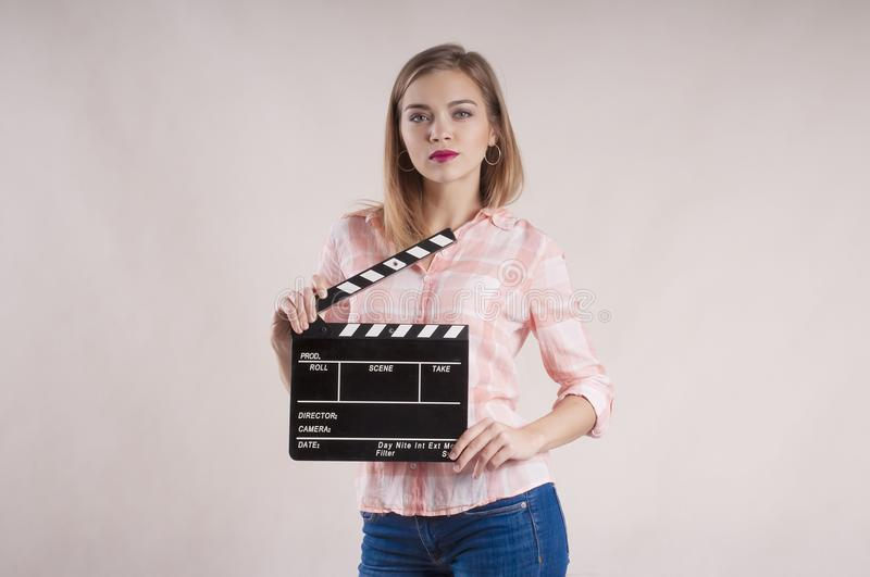 Girl is holding a clapperboard and posing. start on white background. Girl is holding a clapperboard and posing startbackground royalty free stock photos