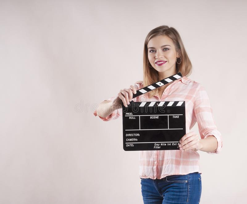 Girl is holding a clapperboard and posing. actioncutproducer start on white background. Girl is holding a clapperboard and posing startbackground producer royalty free stock image