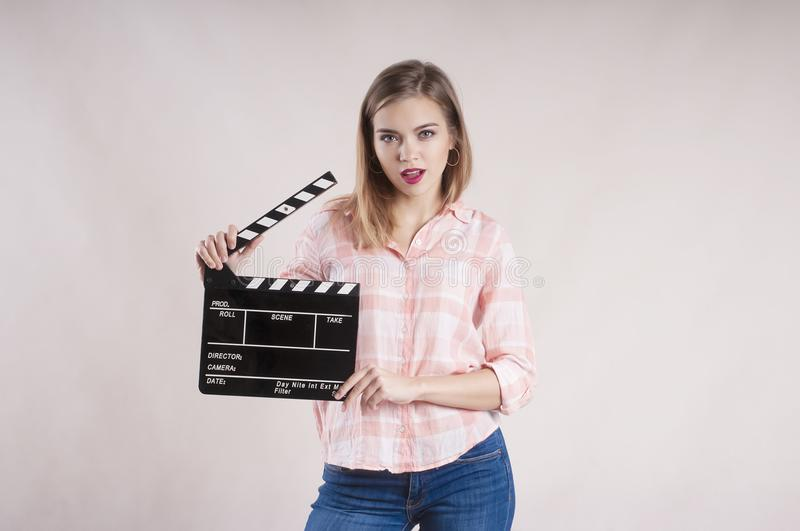 Girl is holding a clapperboard and posing. variation actioncutproducer start on white background. Girl is holding a clapperboard and posing startbackground stock image