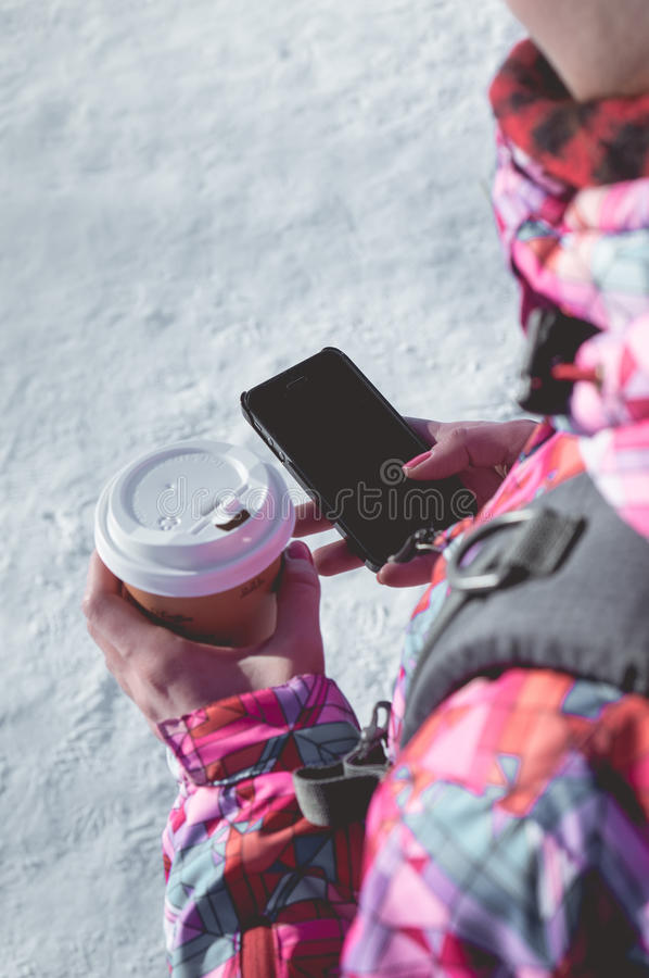 A girl holding a coffee and mobile phone. stock images
