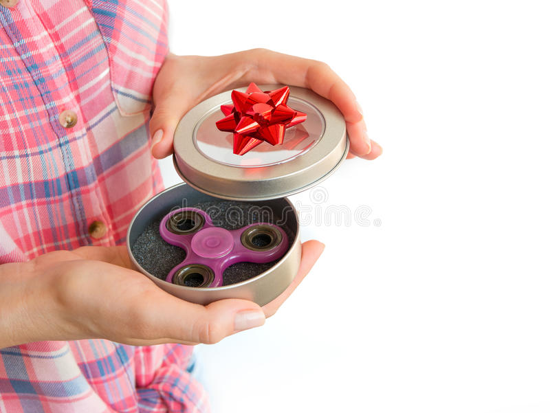 Girl holding a colourful hand fidget spinner toy in a gift box.  stock photo