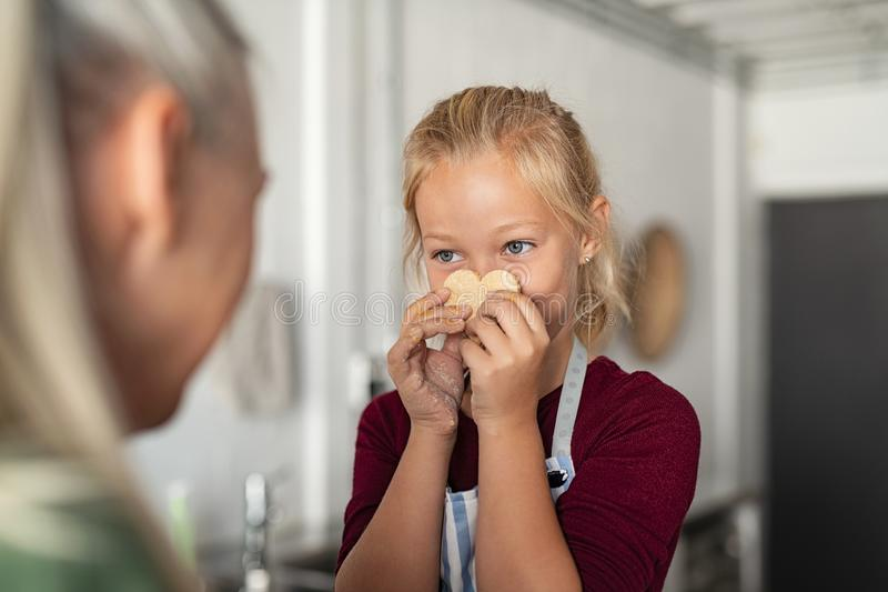 Girl holding cookie with funny face royalty free stock images