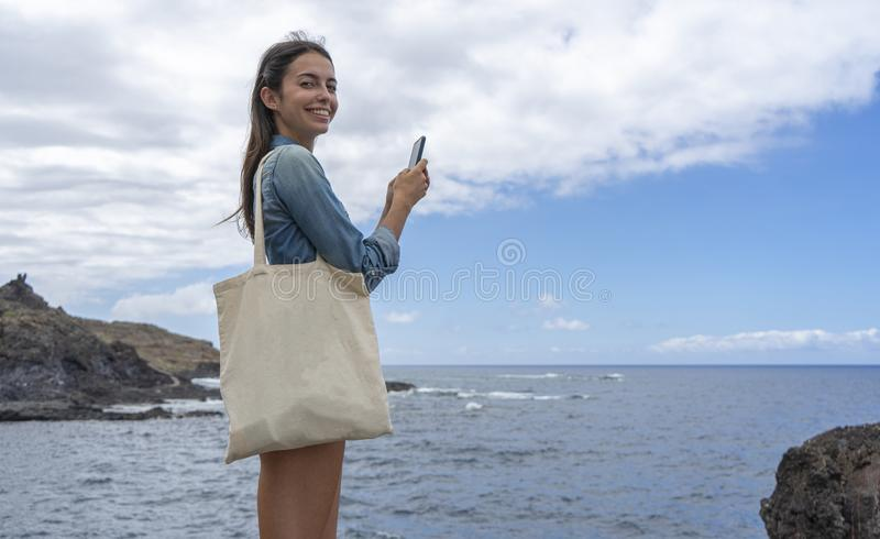 Girl holding cotton canvas while typing with her cellphone in the sea. Conscious Woman using ecology carrier handbag and messaging stock photos