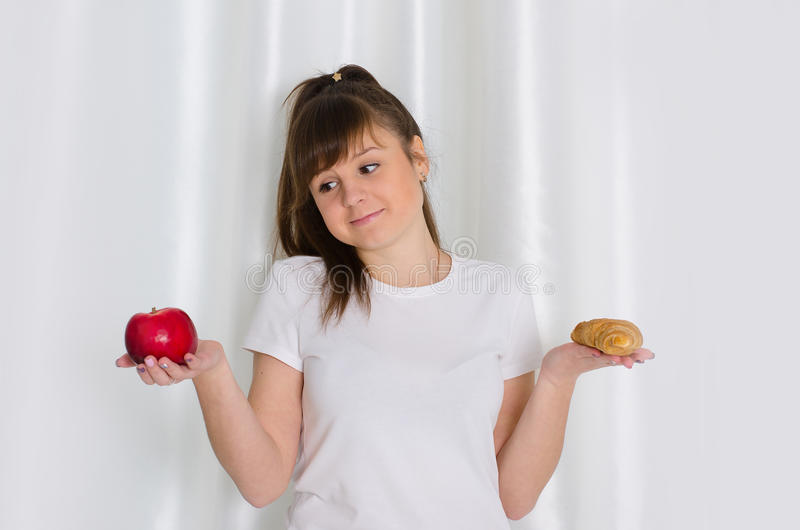 Girl holding croissant and apple stock image