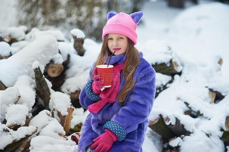 girl holding cup of hot drink and sitting on grass. female hands holding hot chocolate with marshmallow in a red mug. stock photo