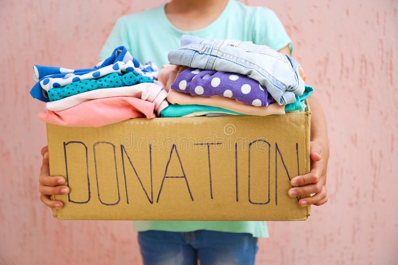 Girl holding donation box with clothes stock photo