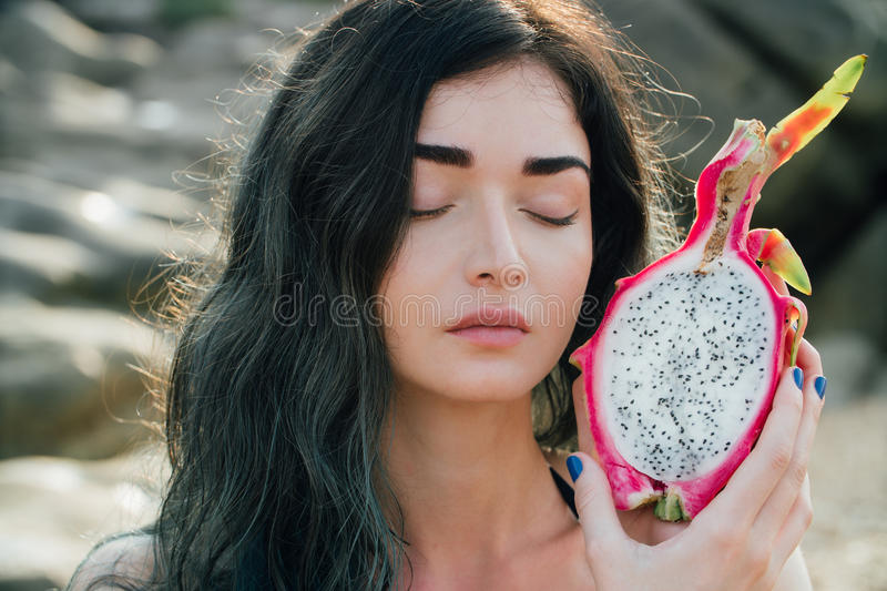 Girl is holding a dragon fruit next to her face. A pitaya fruit holds in hand on the beach. Tropical Dragon Fruit cut in royalty free stock images