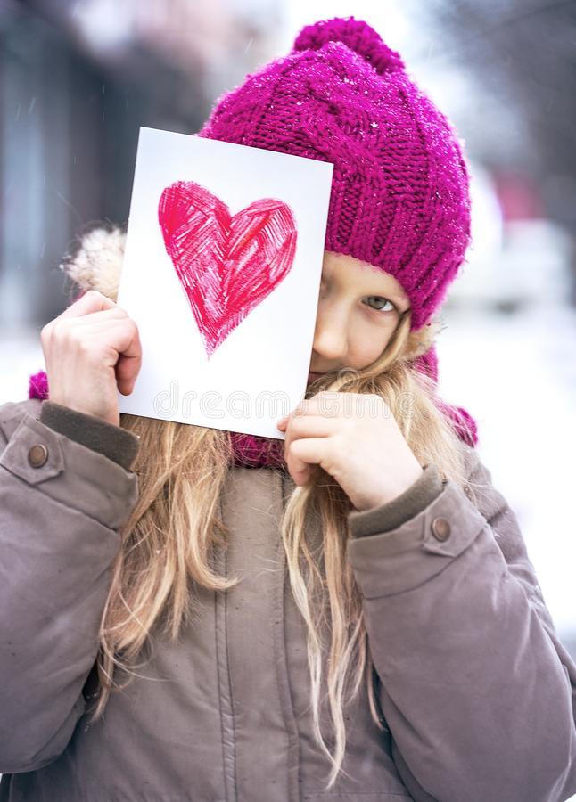 Girl with heart. Girl holding drawing with a heart on the valentines day stock photography