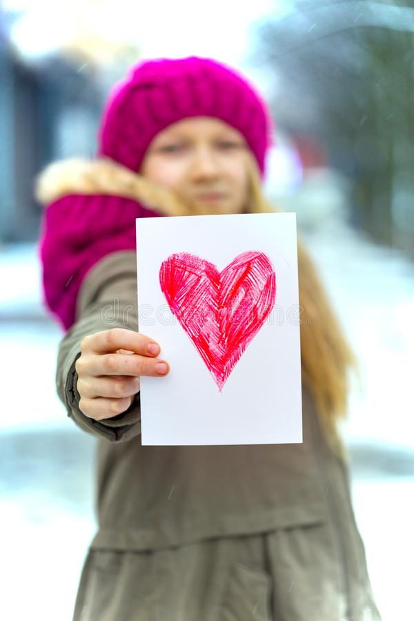 Girl with heart. Girl holding drawing with a heart on the valentines day royalty free stock photography