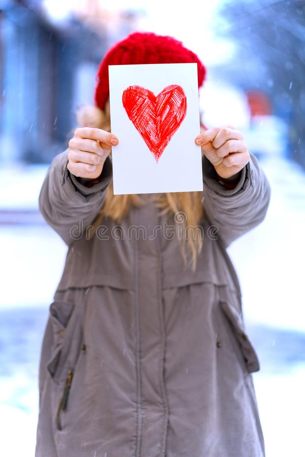 Girl with heart. Girl holding drawing with a heart on the valentines day stock images