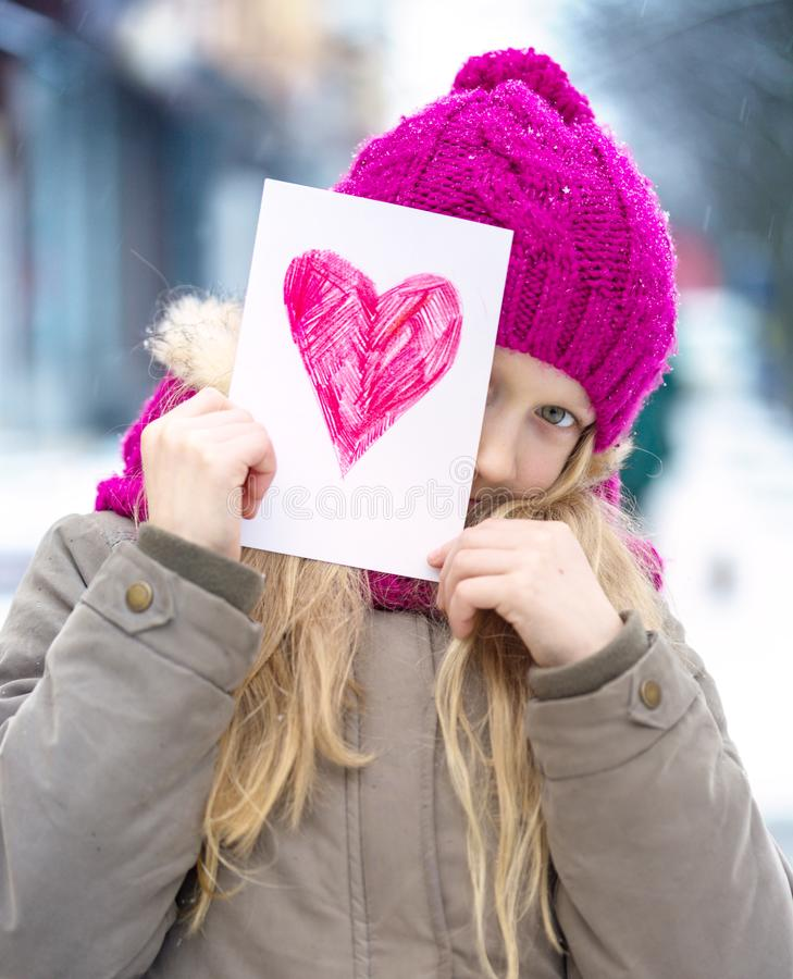 Girl with heart. Girl holding drawing with a heart on the valentines day stock image