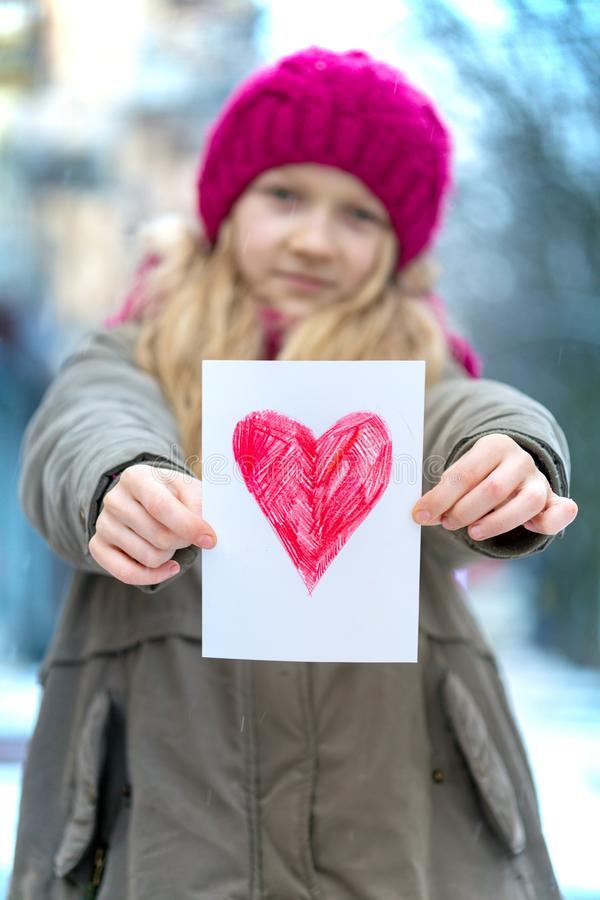 Girl with heart. Girl holding drawing with a heart on the valentines day stock photo