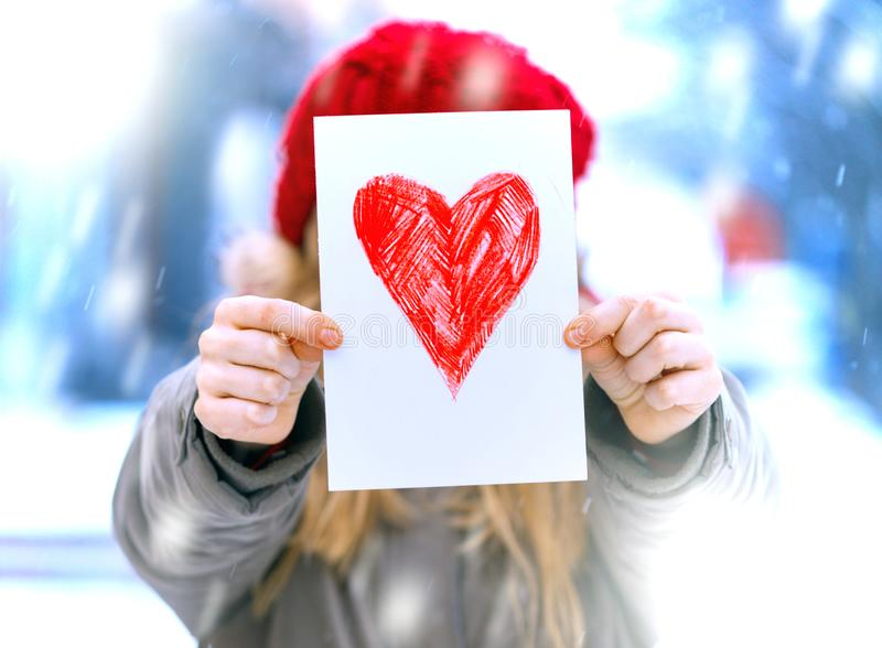 Girl with heart. Girl holding drawing with a heart on the valentines day stock photos