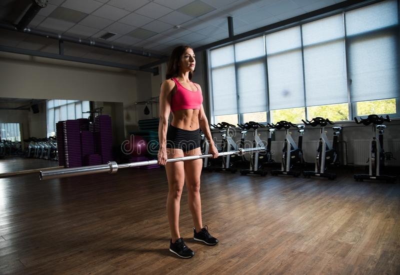 Girl holding an empty rod in the hall of fitness. royalty free stock image