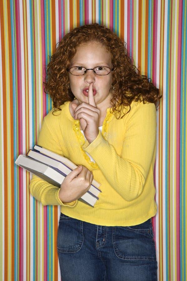 Girl holding finger to lips. Caucasian female child holding books and holding finger to lips royalty free stock photo