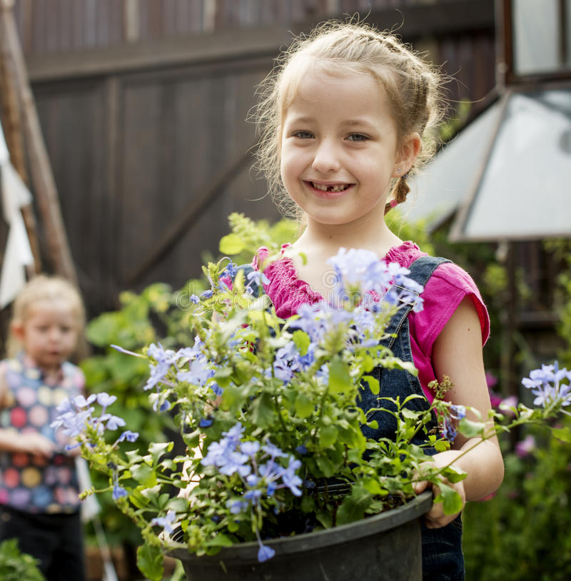 Girl is holding a flower in a garden stock photography