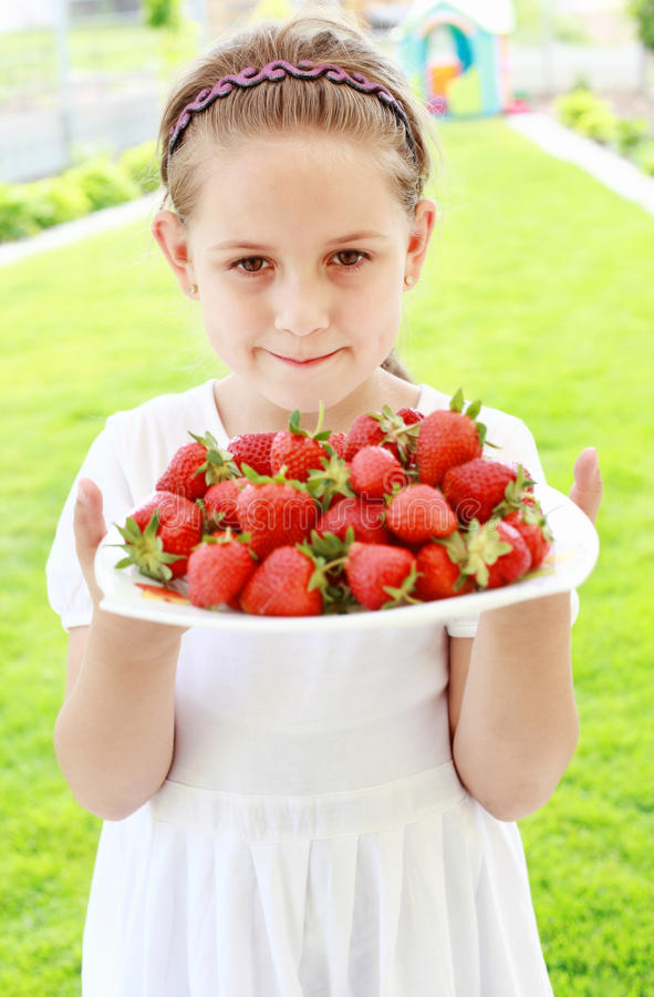 Girl holding fresh strawberries royalty free stock photography
