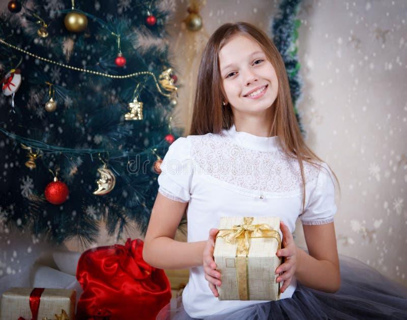 Girl holding gift box under Christmas tree royalty free stock image