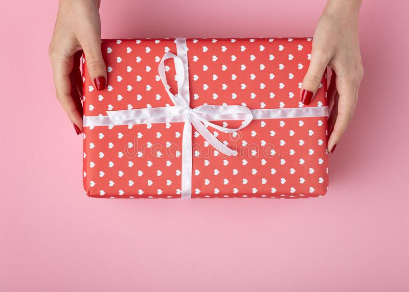 Girl holding gift in hands, box wrapped in decorative paper on a pastel colored pink background, top view, concept holiday and stock images