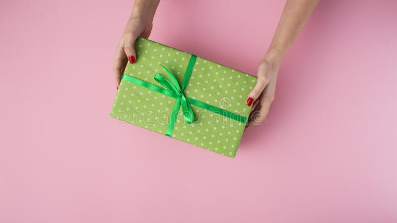 Girl holding gift with hearts in hands, box wrapped in decorative paper on a pastel colored pink background, top view, concept stock photo