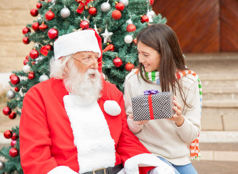 Girl Holding Gift While Looking At Santa Claus royalty free stock image