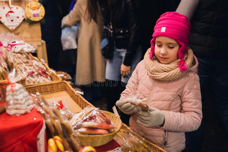The girl holding a gingerbread on Christmas Market at St. Stephen`s Square in front of the St. Stephen`s Basilica. royalty free stock photos