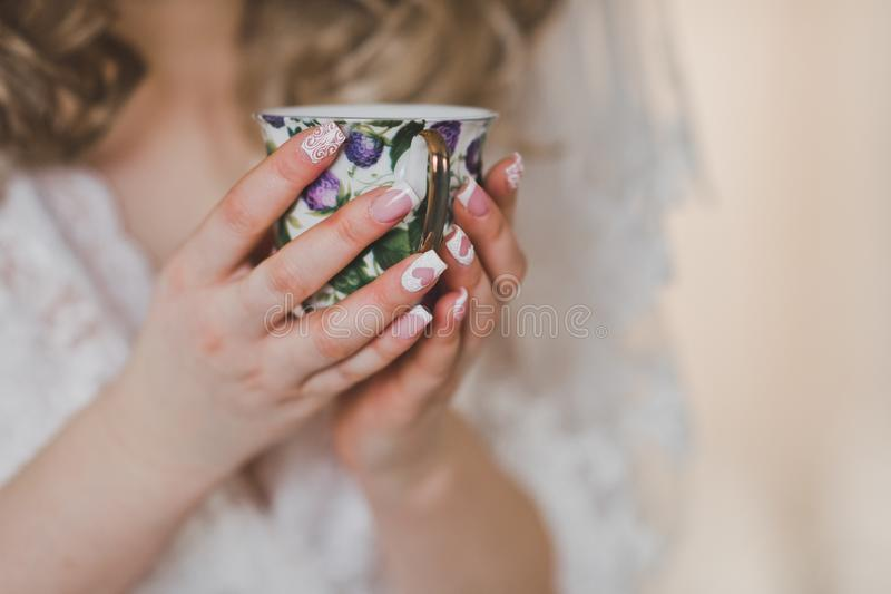 A patterned glass of tea in the hands of a woman royalty free stock image
