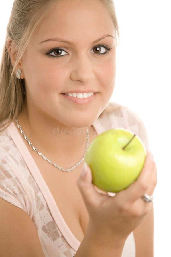 Girl holding green apple stock photography