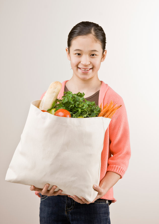 Girl holding grocery bag full of fruit royalty free stock photography