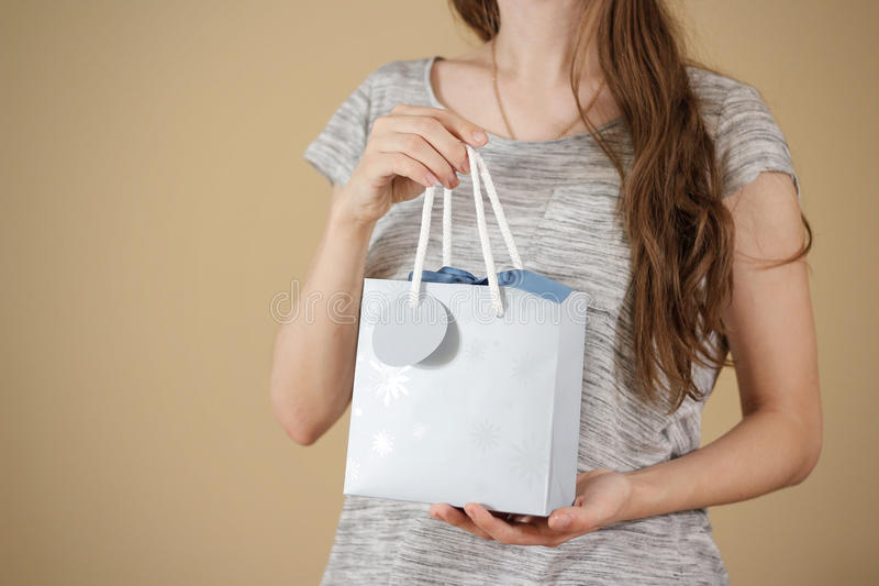 Girl holding in hand blank blue paper gift bag mock up. Empty pa stock photo