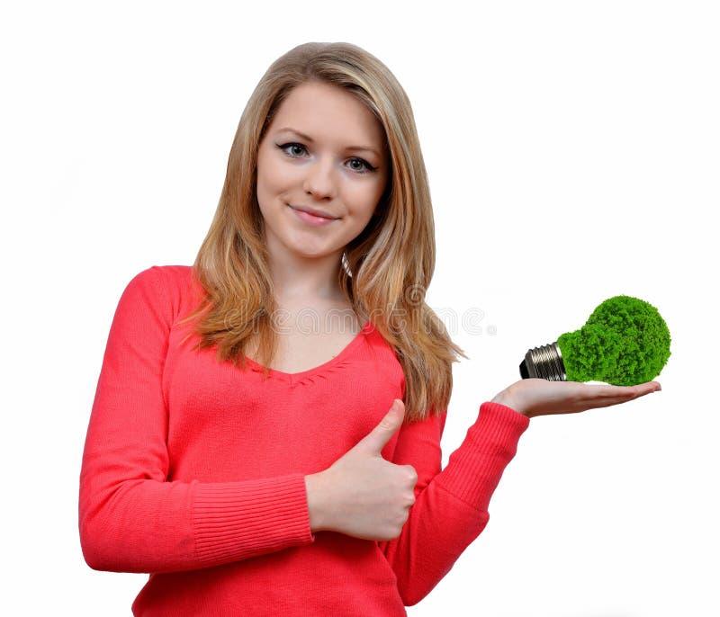 Girl holding in hand eco energy bulb