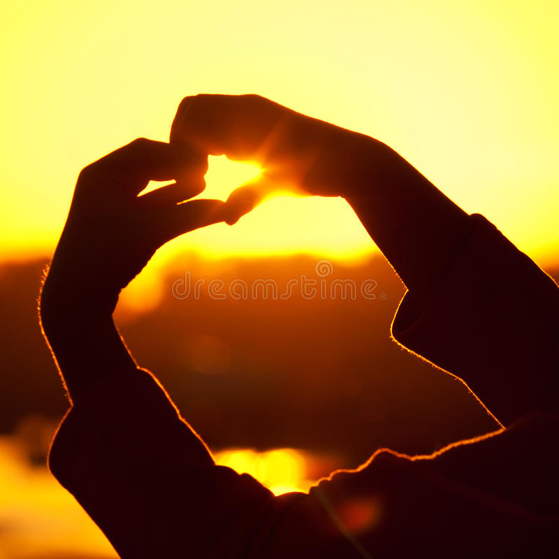 Girl Holding In Hands The Setting Sun Stock Images