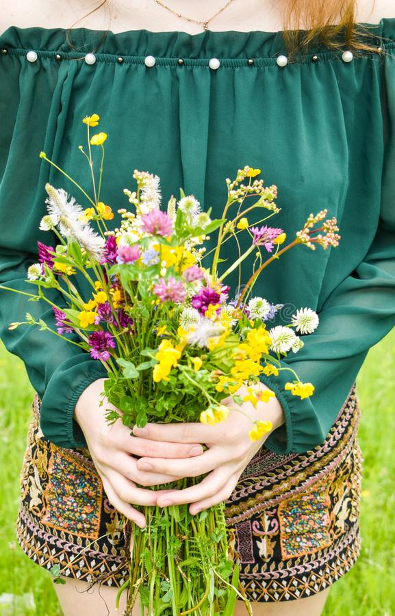 Girl holding in her hand a beautiful bouquet with multi-colored wild flowers. Amazing bunch of wilf flowers in the nature royalty free stock photos