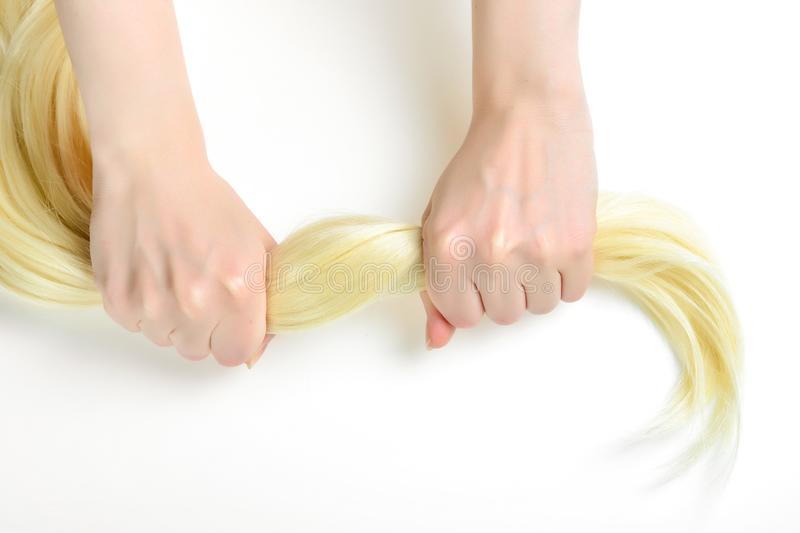 Girl is holding her healthy strong blond hair stock image