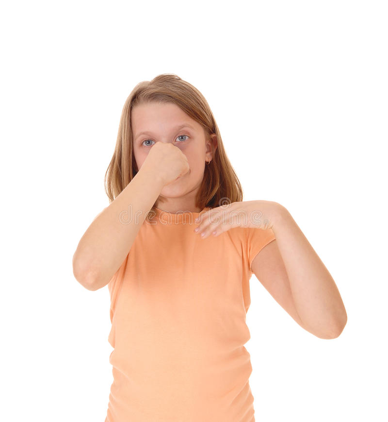 Girl holding her nose. A little young girl standing for white background holding her nose closed for the bad smell around her stock photography
