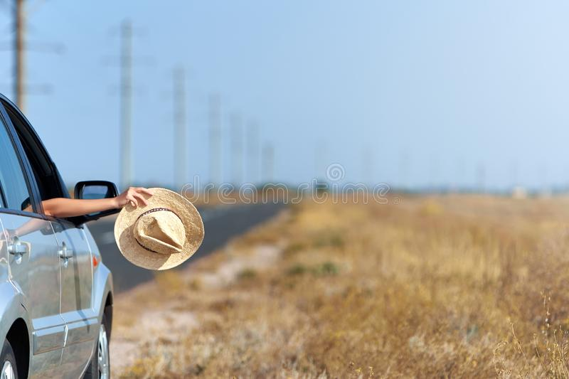 Girl holding her straw hat in hand on summer road trip. Woman put hat out of the car window drive away in vehicle. Travel lifestyle concept. Girl holding her royalty free stock photography