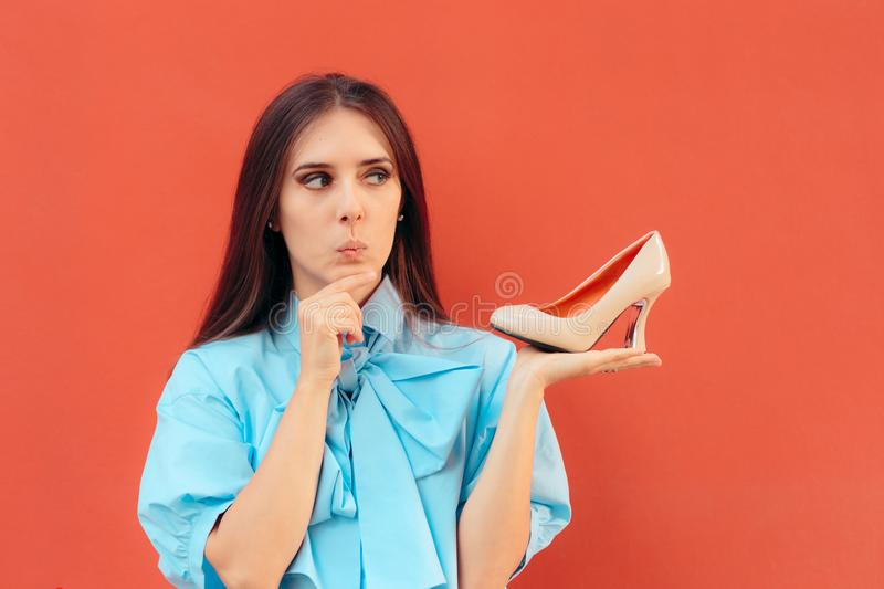 Girl Holding a High Heel Shoe Thinking about Wearing it stock image