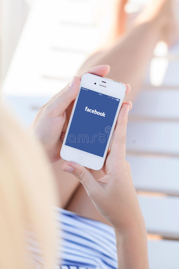 Girl in a holding iPhone with Facebook screen royalty free stock photography