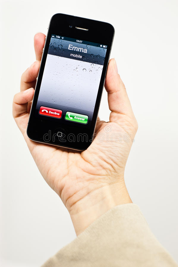 Girl holding iPhone with incoming call. A girl's hand holds an iPhone showing on screen an incoming call royalty free stock photography