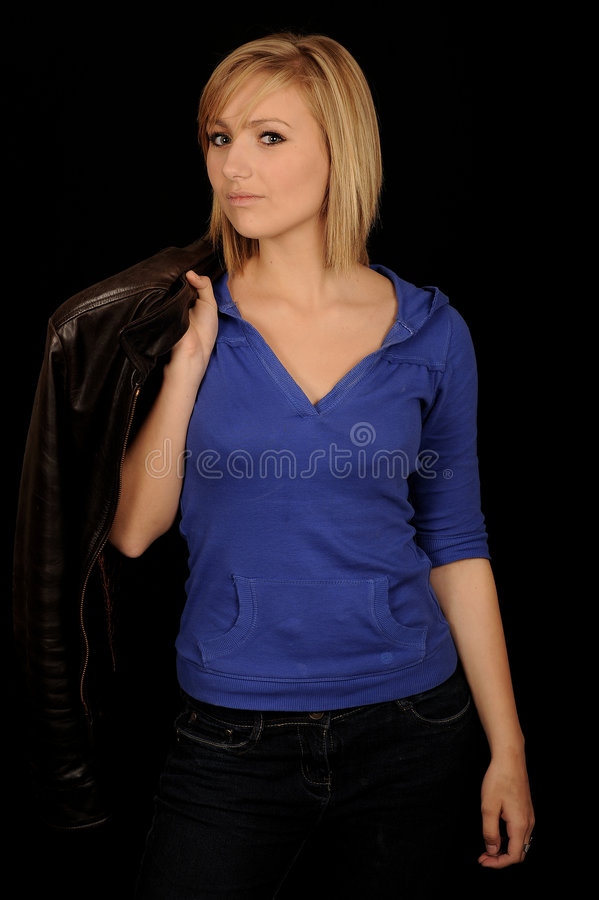 Girl holding jacket. Young woman holding her jacket over her shoulder. Isolated against a black background royalty free stock image