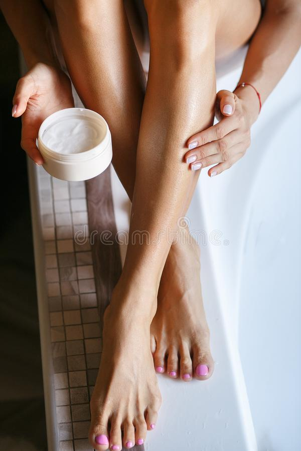 The girl is holding a jar of moisturizing cream in her hands. She smears her feet with her fingers stock photography