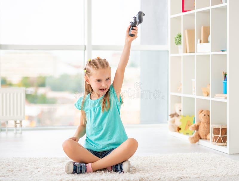 Girl holding joystick. Happy little girl holding joystick above her head in light room royalty free stock image