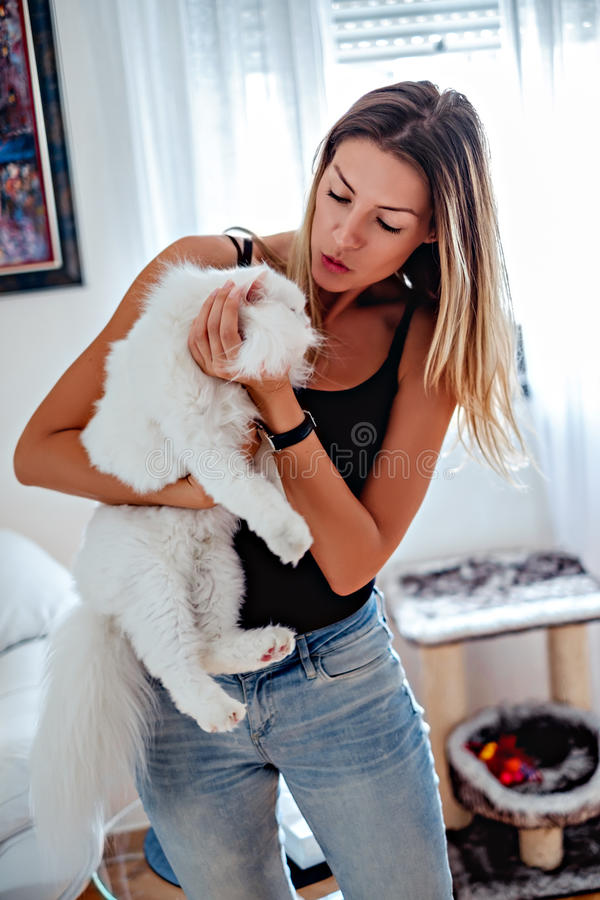 Girl holding and kissing her white persian cat royalty free stock photo